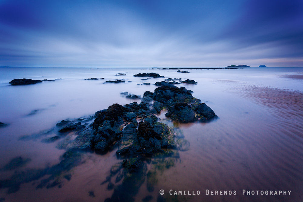 Cloudy conditions prevented a spectacular sunrise from happening, but the blue hour light in combination with the radiating clouds was wonderful. Yellowcraig Beach near North Berwick, East Lothian.
