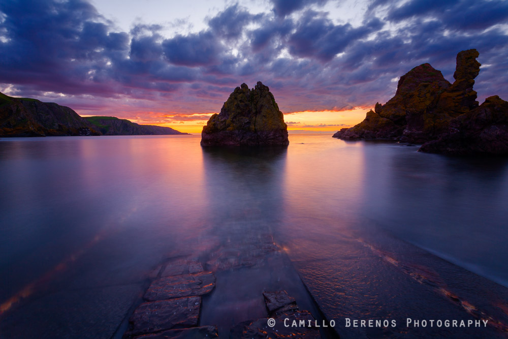 Jetty at St Abbs Head submerged at high tide during an intense sunset in summer.