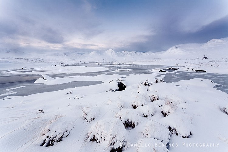 A partially frozen Lochan na Stainge with the snow-covered mountains of Black Mount behind