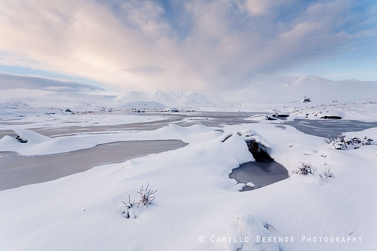 Soft morning light over a frozen Lochan na Stainge and snow-covered Black Mount mountains