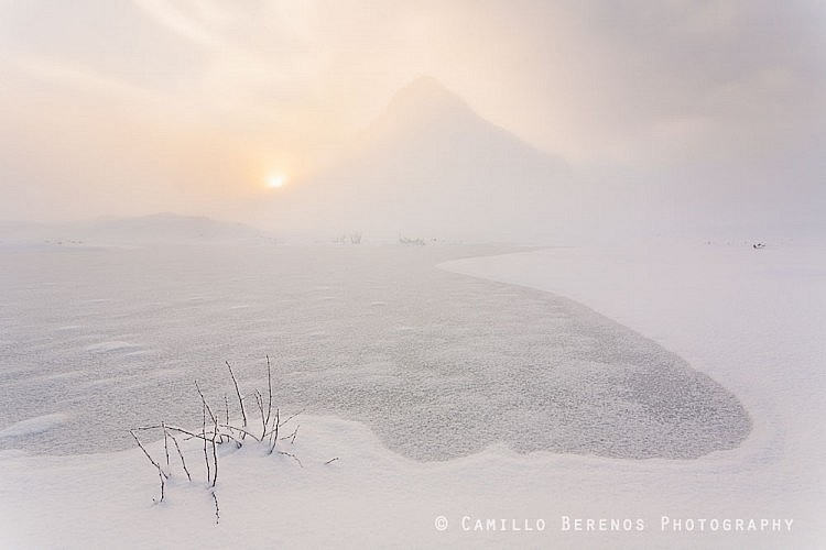 A frozen lochan lies in front of the snow-covered Buachaille Etive Beag, partly obscured by low hanging cloiuds.