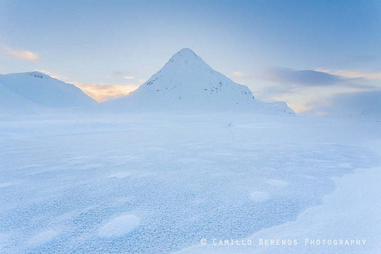 A frozen lochan with the Buachaille Etive Beag behind it during the blue hour after sunset.
