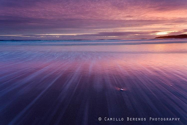 Retreating waves creating streaks on Tyninghame beach at sunrise.