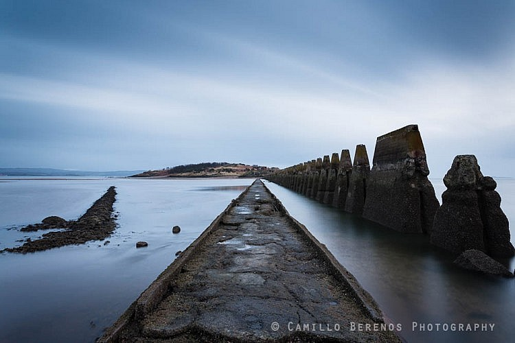 The causeway to Cramond island near Edinburgh as the tide rolls in on a cloudy morning.