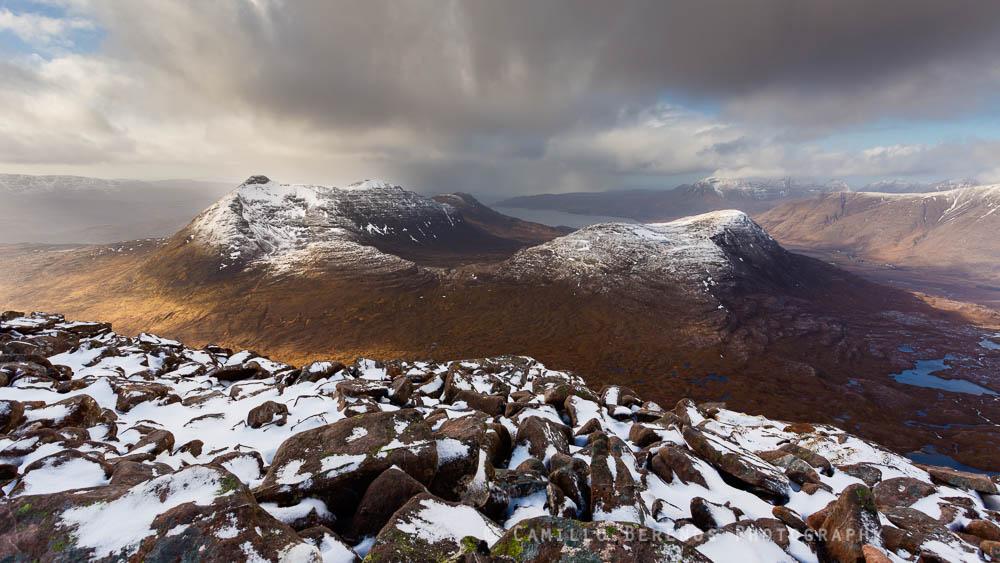 Dramatic sky over a snow-capped Beinn Damh from Maol Chean-dearg, Torridon, Scotland