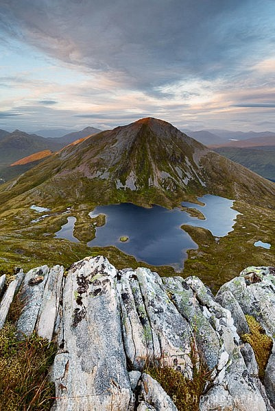 Sgurr Eilde Mor partially turning red by the setting sun with rocks on Sgor Eilde Beag in the foreground