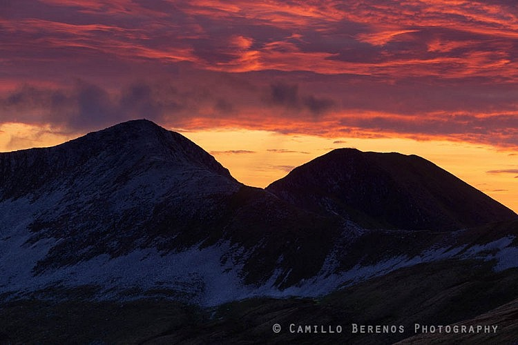 The sky turning vibrant red behind Na Gruagaichean at sunset