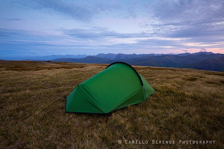 A tent pitched while wild camping in the Mamores, Scotland, with the mountain massifs of Glen Coe in the background