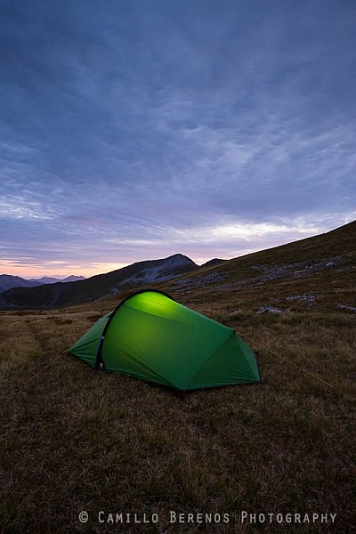 Torch lit tent high up in the Mamores while wild camping in Scotland