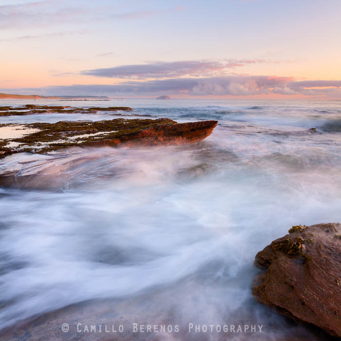 Strong currents are formed when the waves are funneled through this narrow chute in between rocks at Tyninghame beach, East Lothian. As the sun had just risen, the light was beautifully soft and warm.