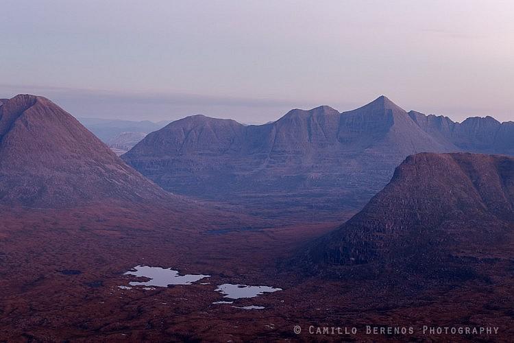 The primordial landscape of Torridon (Beinn Eighe, Liathach and Carn na Feola) unfolds below Beinn na Eoin at dusk.