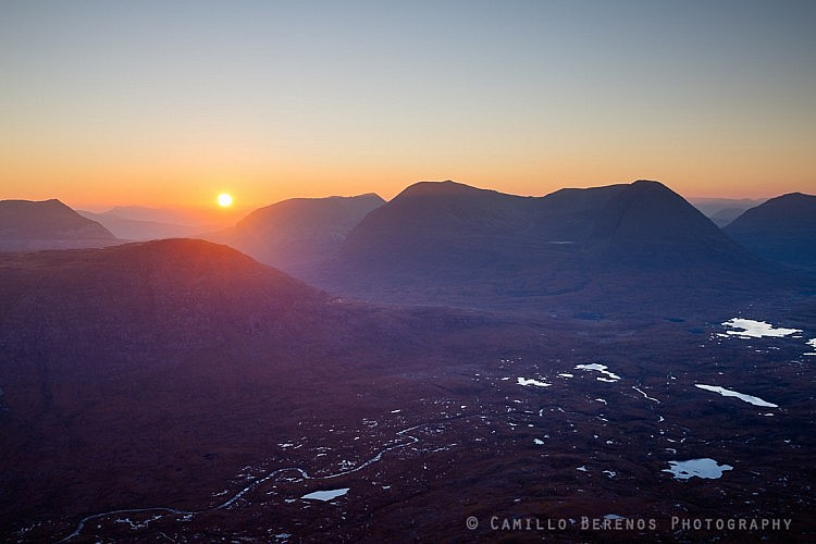 The sun rising above the rugged landscape of Torridon with Beinn a 'Chearcaill and Beinn Eighe towering high above the moorland.