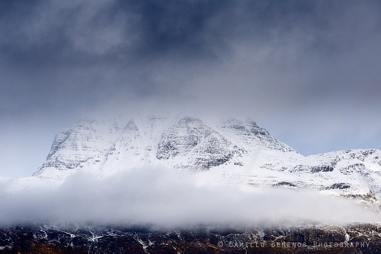 A band of low hanging clouds at the foot of a snowcapped Slioch