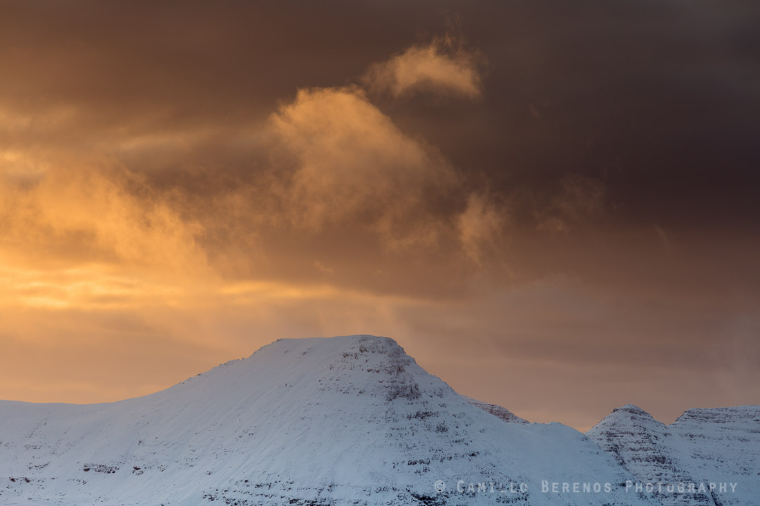 Brightly lit clouds above Beinn Dearg stand out against a backdrop of dark snow clouds at sunset