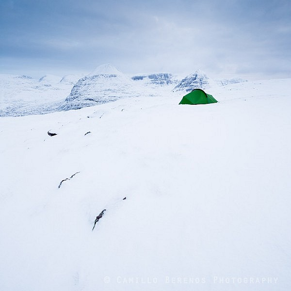 A tent pitched in the snow of the Torridon hills while wild camping in winter