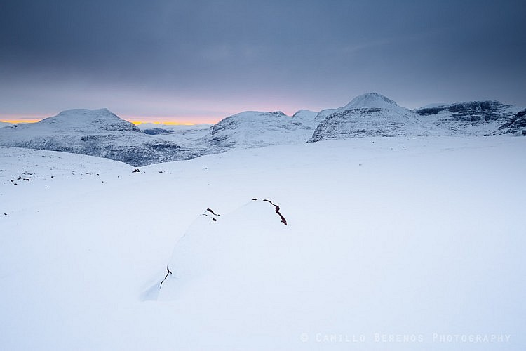 A hint of the imminent sunrise behind Beinn Eighe and Meall a' Ghiubhais in winter