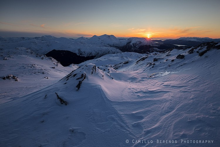 The sun setting behind the Arnisdale hills, with the Black Cuillin on the Isle of Skye on the far right