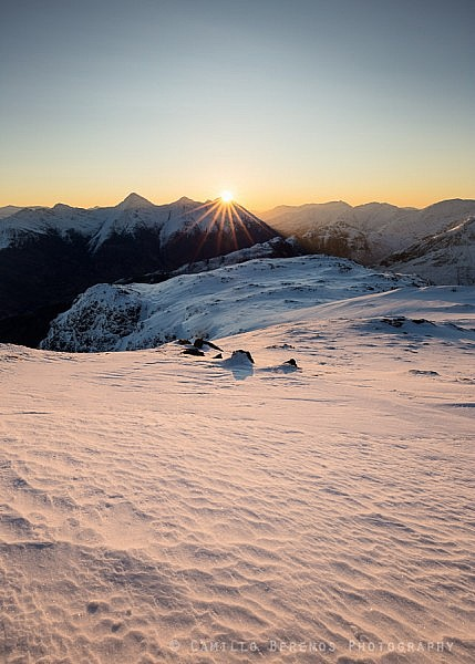 After a long cold night the sun finally rises above the Kintail ridge while illuminating the textured snowy foreground