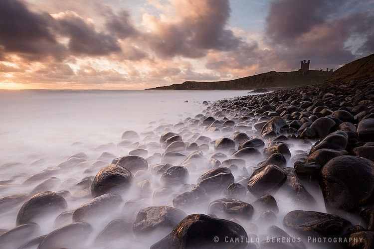 Stormy seas at Embleton Bay with Dunstanburgh Castle perched high on the cliffs beyond
