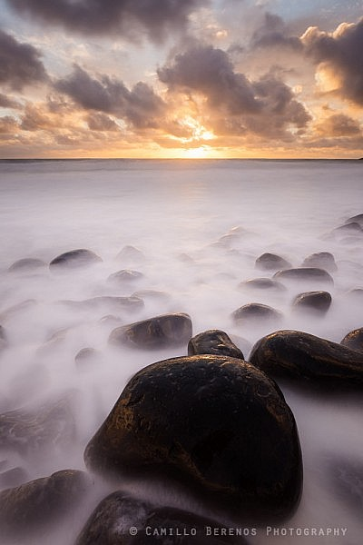 Boulders at Embleton Bay softly lit by the rising sun