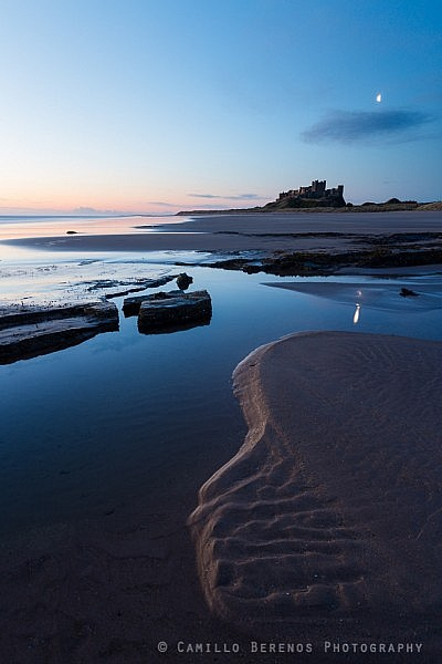 Moon over Bamburgh castle at dawn