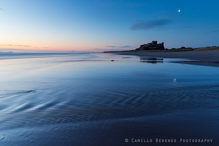 Bamburgh castle partly reflected in the wet sand of the beach as the waves retreat