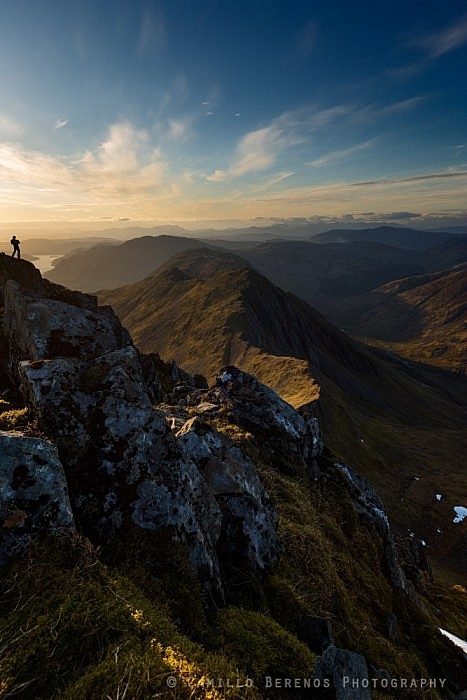 A landscape photographer on the steep slopes of Sgurr Fhuaran capturing Sgurr nan Saighead and the vast landscape of Kintail at sunset