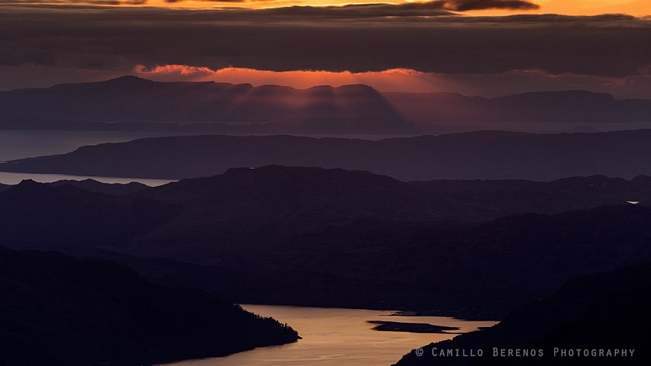 Sunbeams piercing through the clouds above Loch Duich as the sun sets