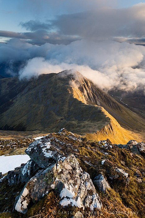 Clouds coming in over the summit of a sidelit Sgur nan Saighead at sunrise