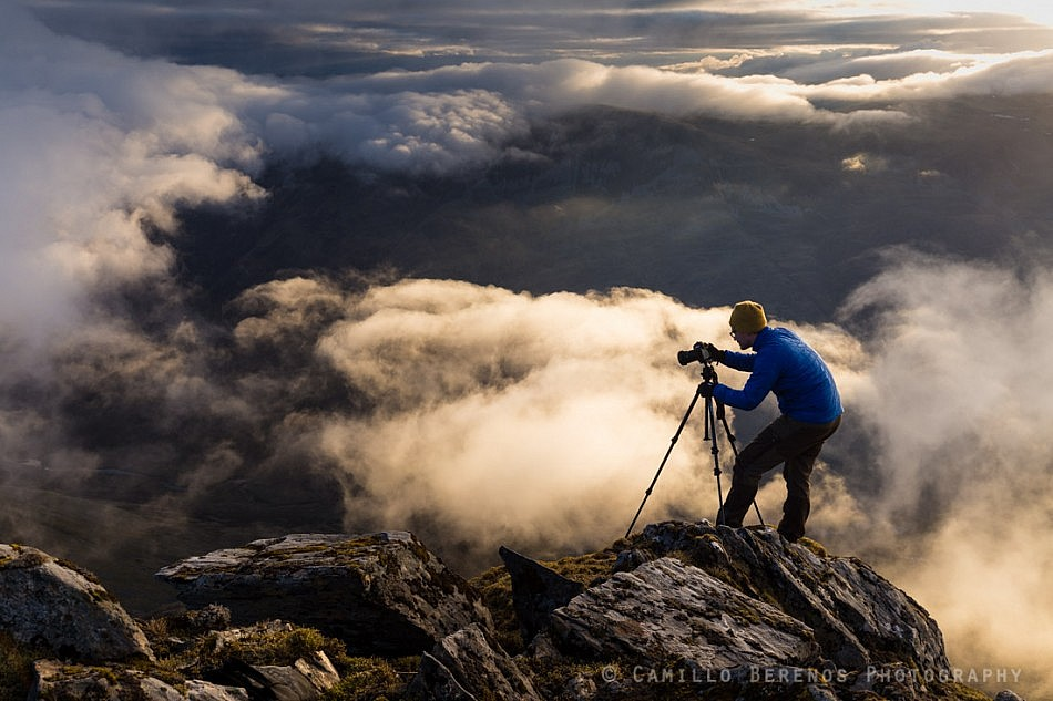 A landscape photographer setting up for his shot above the clouds on a steep cliff in the Scottish Highlands (Sgurr Fhuaran, Five Sisters of Kintail)
